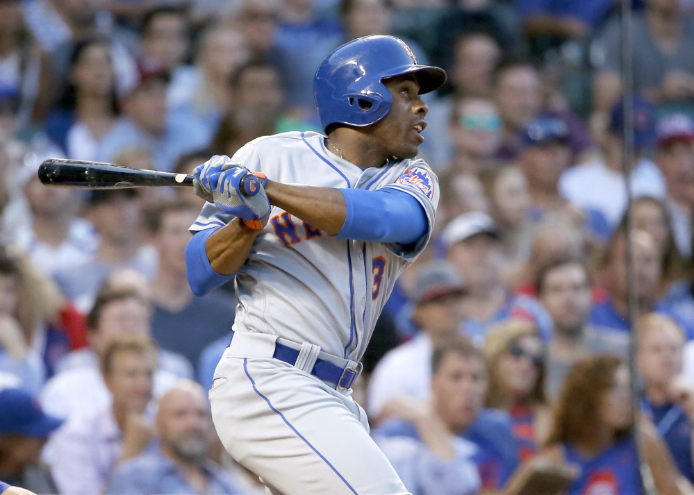 Curtis Granderson of the Mets hits a sacrifice fly off Chicago Cubs starting pitcher Jake Arrieta, scoring Jose Reyes, during the sixth inning of Tuesday's game, won by the Mets in Chicago.