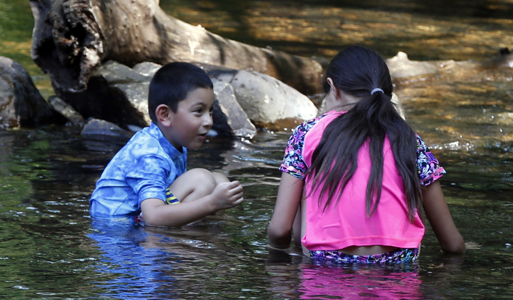 Two children cool off in Minnehaha Creek as oppressive heat and tropical humidity move the heat index to over 100 degrees Wednesday in Minneapolis.