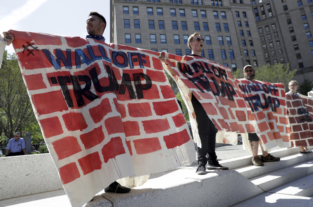 Immigrant rights activists hold up a fabric wall to protest against Republican presidential candidate Donald Trump on Wednesday in Cleveland, during the third day of the Republican convention.
