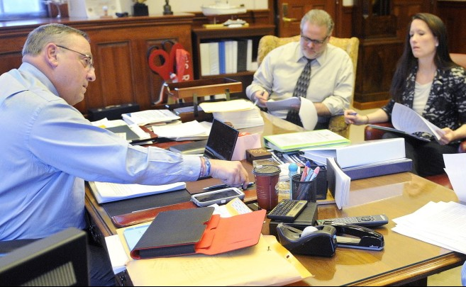 Gov. LePage works on his third State of the State address in 2014, with staffers including press secretary Adrienne Bennett and communications director Peter Steele. LePage has asked his employees to communicate with handwritten notes that are never archived.