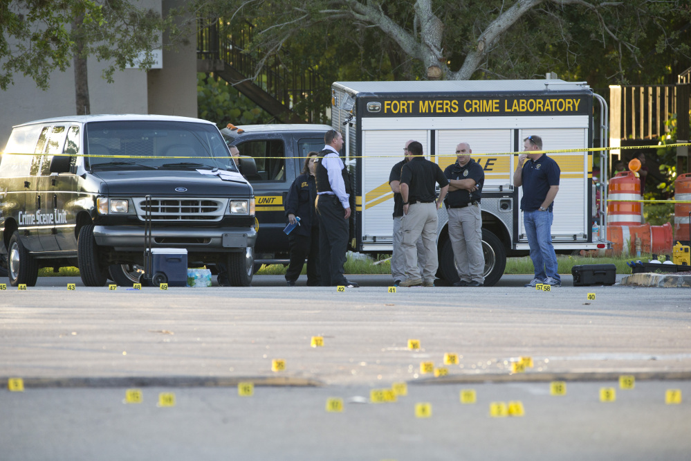 A Fort Myers Crime Laboratory vehicle and yellow evidence markers are at the scene of a deadly shooting outside of Club Blu in Fort Myers, Fla., on Monday.