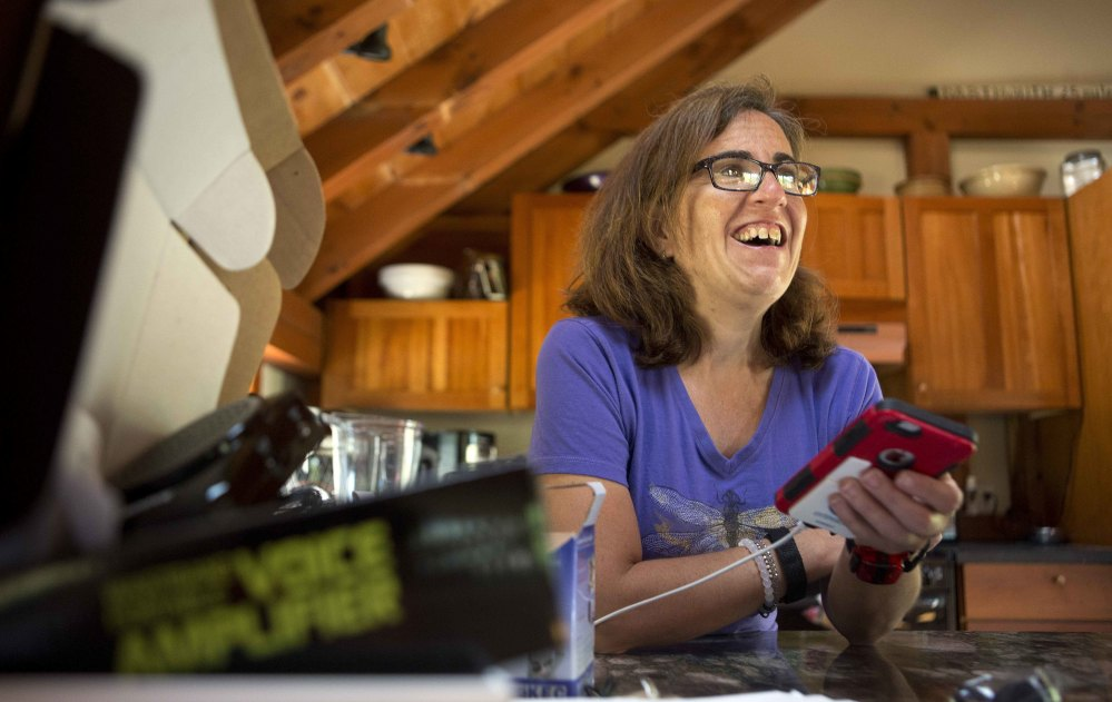 Jessie Levine listens to her recorded outgoing phone message on her iPhone in Springfield, N.H. Levine's own tones were blended with a relative's voice to re-create what she sounded like before Lou Gehrig's disease robbed her of her speech.