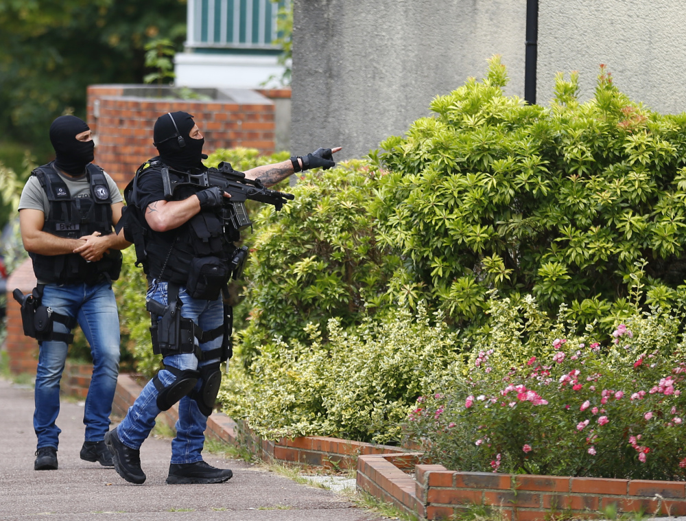 Hooded police officers conduct a search in Saint-Etienne-du-Rouvray, Normandy, France, following an attack at a church that left a priest dead Tuesday.
