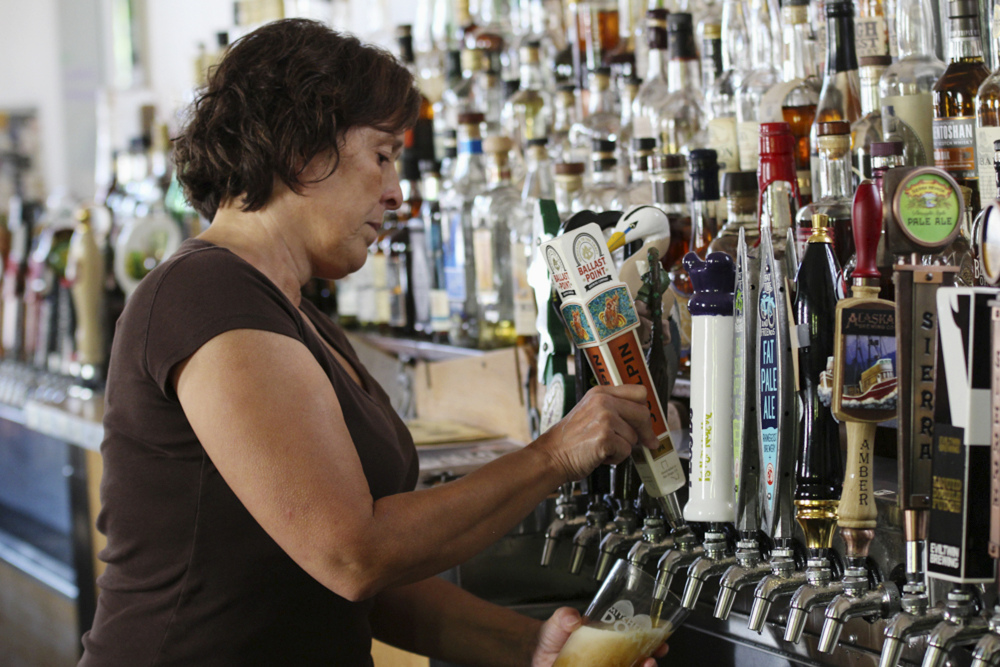 Bartender Catherine Pierluissi pulls a Ballast Point tap handle at Sugar Maple in Milwaukee, where there are at least 60 beers on tap.