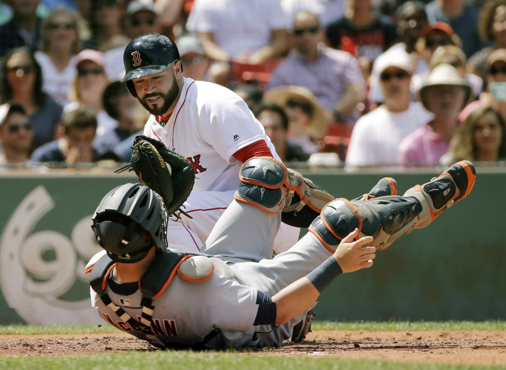 Detroit catcher James McCann hangs onto the ball after tagging Boston's Sandy Leon out at the plate trying to score on a fly ball by Mookie Betts in the third inning of Wednesday's game at Fenway Park in Boston.