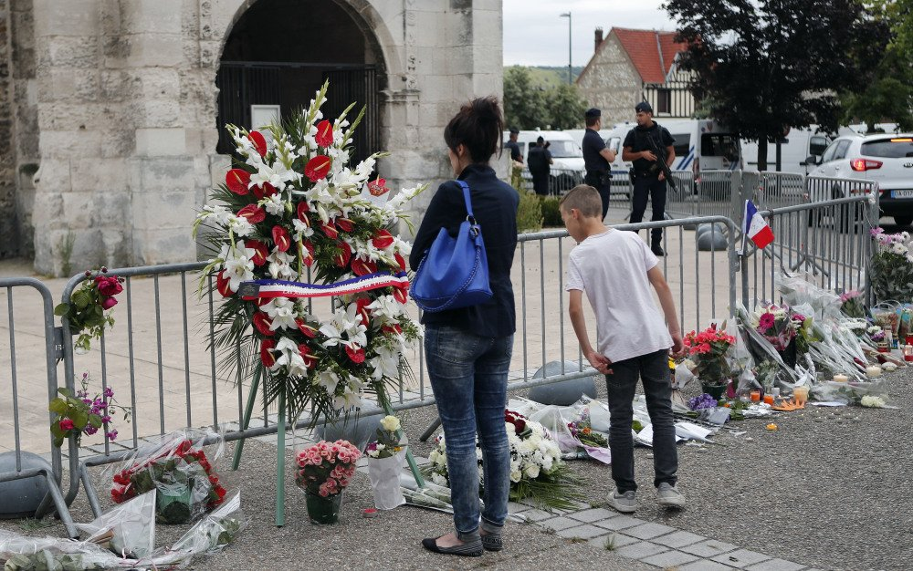 People pay respects Wednesday outside a church in the village of Saint-Etienne-du-Rouvray, in Normandy, France, where an 85-year-old priest was slain Thursday.