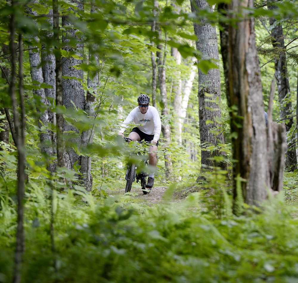 Ian Stewart, executive director of the Coastal Mountains Land Trust, bikes on what will soon be the Round the Mountain trail at Ragged Mountain in Camden.