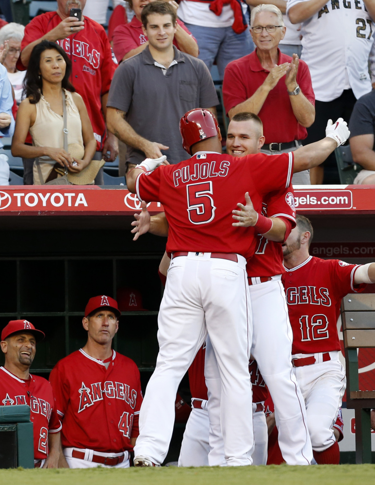 Albert Pujols of the Los Angeles Angels is congratulated by Mike Trout after hitting a two-run homer in the third inning Saturday night against Boston.