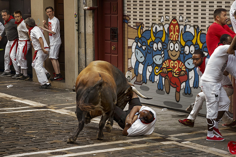 A reveler is gored by a fighting bull during the running of the bulls in Pamplona, Spain on Friday.