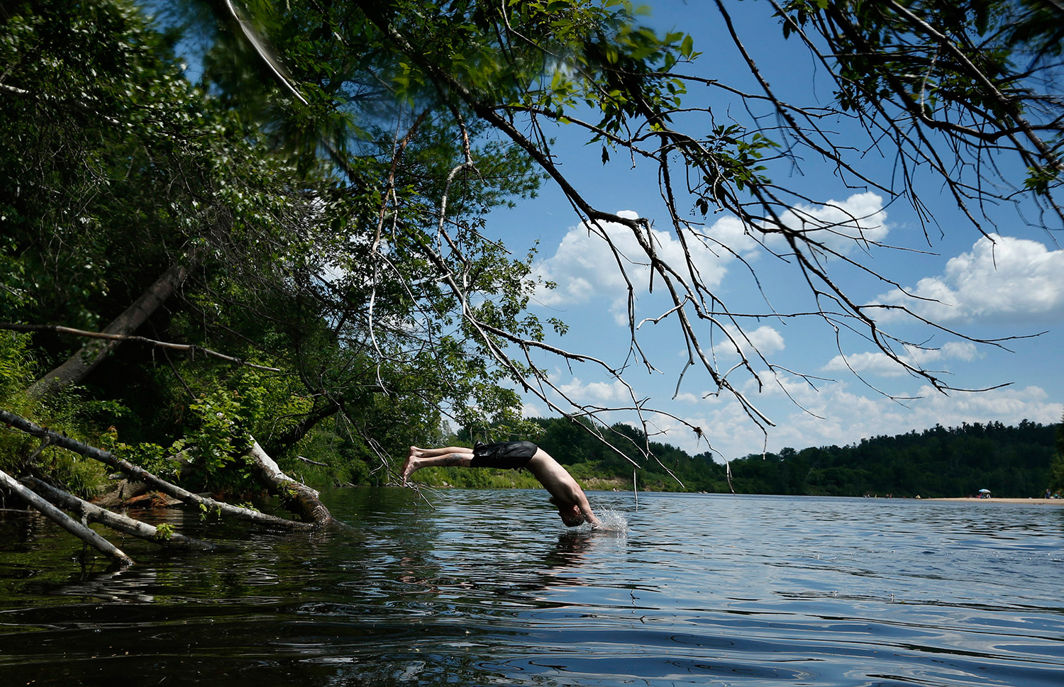Kenny Bachman, of Brownfield, dives into the Saco River on Wednesday in Fryeburg. Thunderstorms on Thursday could cools things off.