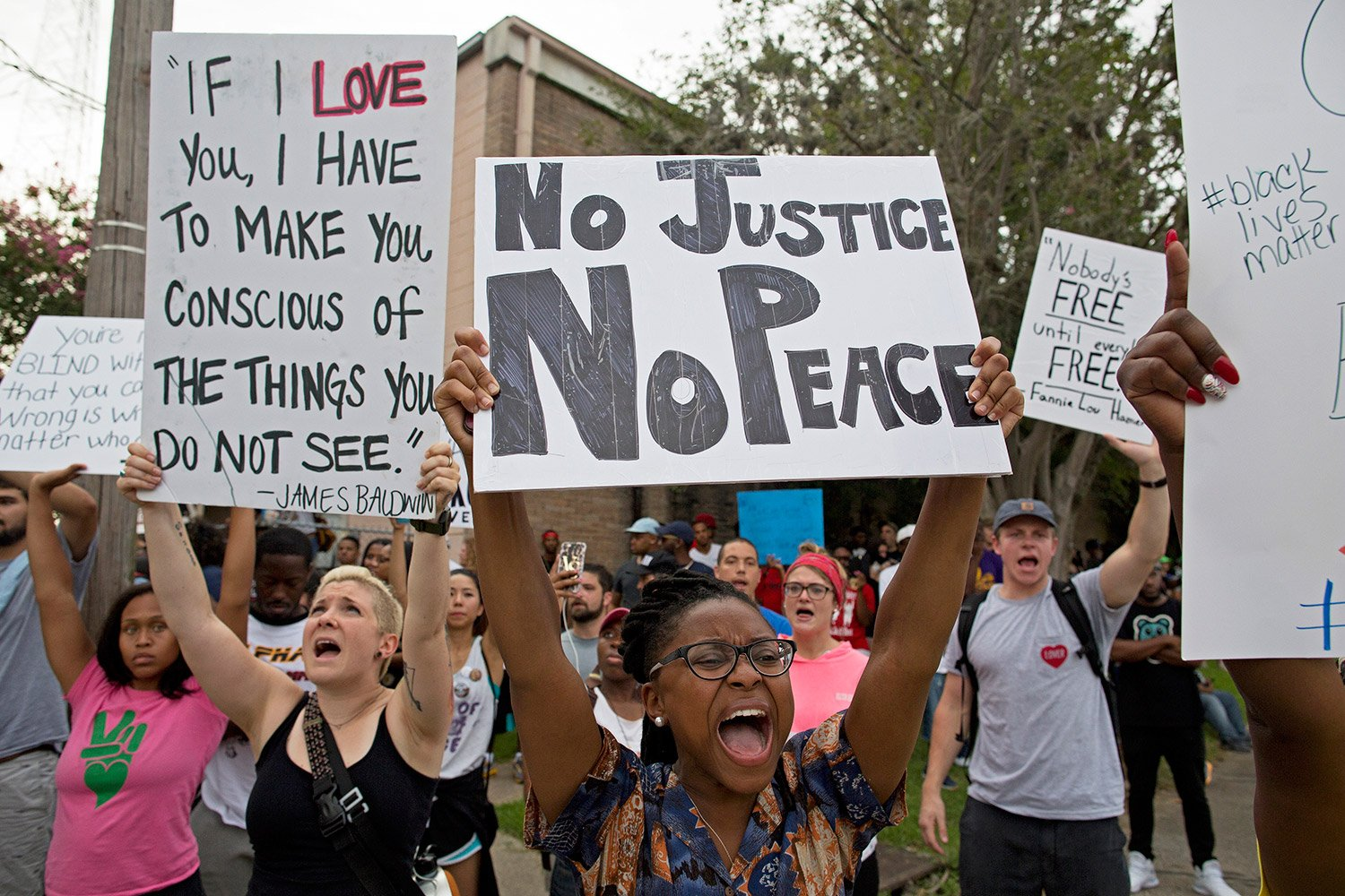 Protesters hold signs as they march through a residential neighborhood in Baton Rouge.