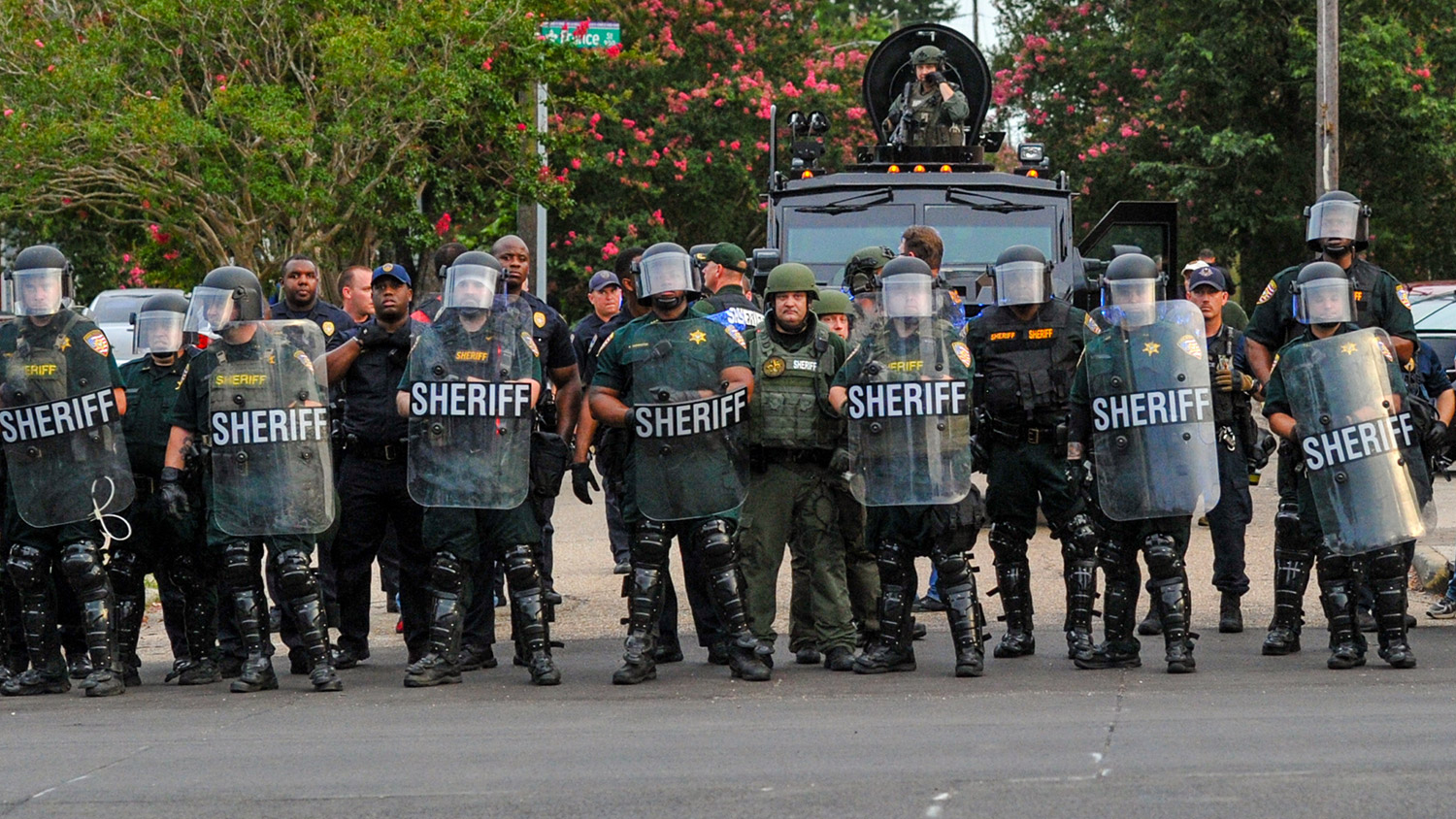 Police officers watch protesters gathering against another group of protesters in Baton Rouge, La.
