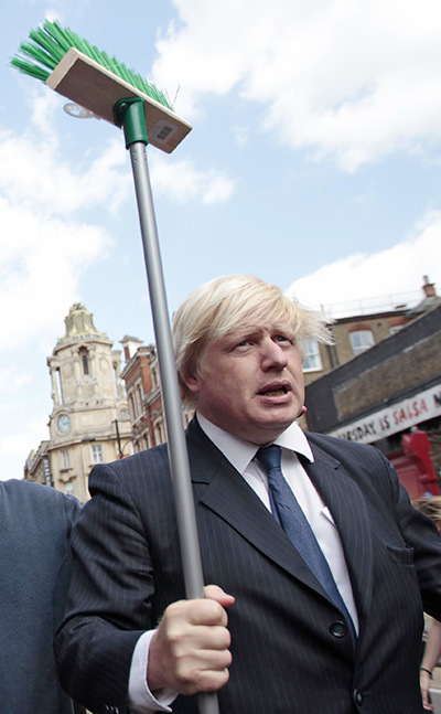 Then-London Mayor Boris Johnson brandishes a broom during a visit to meet residents in an area of the city affected by rioting in 2011. He was seen as an effective cheerleader for London during his stint as mayor, a tenure that included the successful 2012 Summer Olympics.
