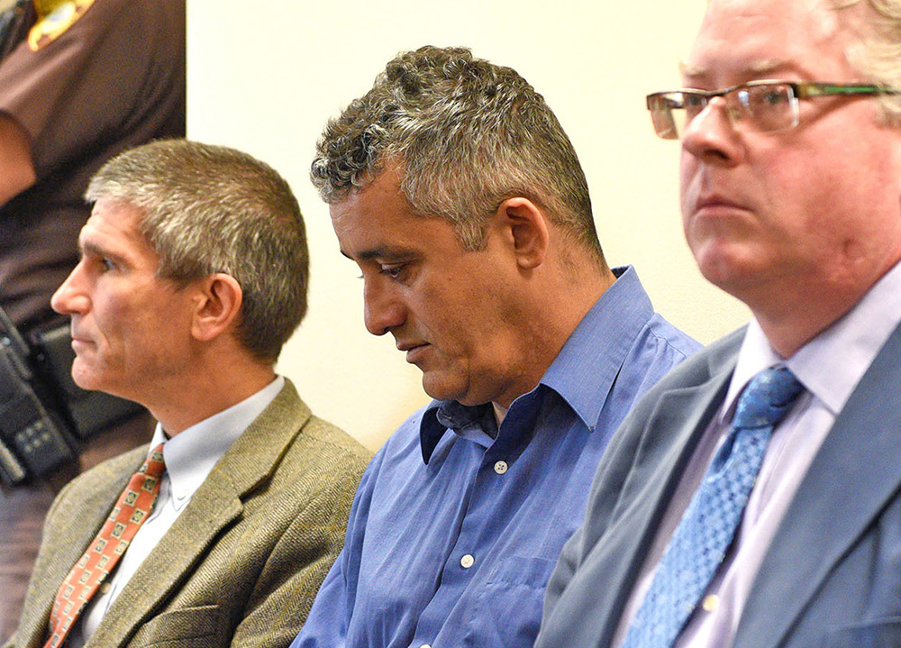Former Dartmouth professor J. Martin Favor, center, waits for his probable cause hearing with his attorney, Charlie Buttrey, left, in Claremont, N.H., District Court, on Sept. 14, 2015.  James M. Patterson/Valley News via AP