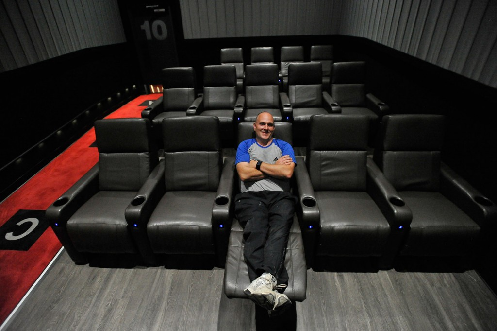 Andrew Poore, vice president of operations for the Flagship cinema chain, stretches out in a recliner in one of the 10 theaters at Flagship Premium Cinemas in Falmouth on Thursday.