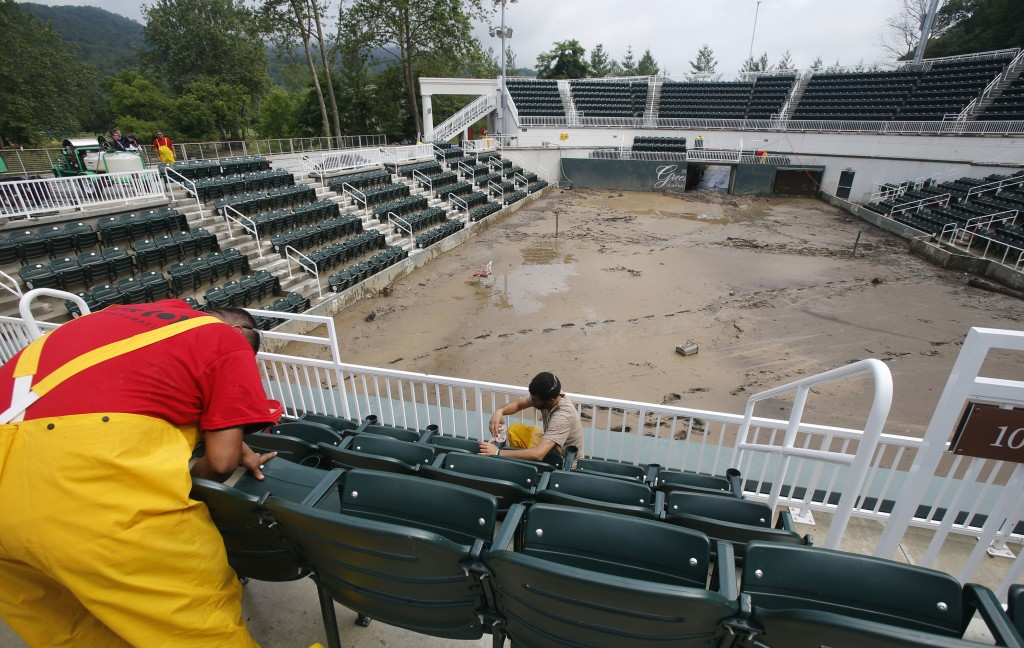 Workers clean seats on June 28 in the stands at Center Court at the Greenbrier Resort in White Sulphur Springs, W. Va. The Greenbrier's 710-room hotel is reopening to the public more than two weeks after the property was ravaged by floods.   Associated Press/Steve Helber