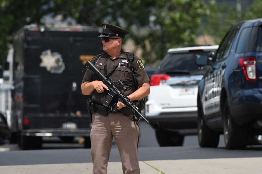 Sheriff's Deputy Guy Puffer stands watch outside the Berrien County Courthouse after Monday's shooting. A jail inmate trying to escape grabbed a gun from an officer, killing two bailiffs before he was fatally shot by other officers. Mark Parren via AP