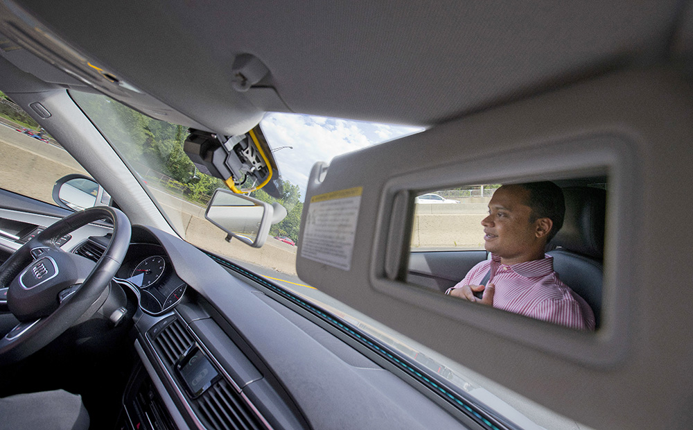 Kaushik Raghu, senior staff engineer at Audi, is reflected in the passenger-side visor mirror while demonstrating a self- driving vehicle on I-395 n Arlington, Va., Friday, July 15, 2016. Pablo Martinez Monsivais/Associated Press