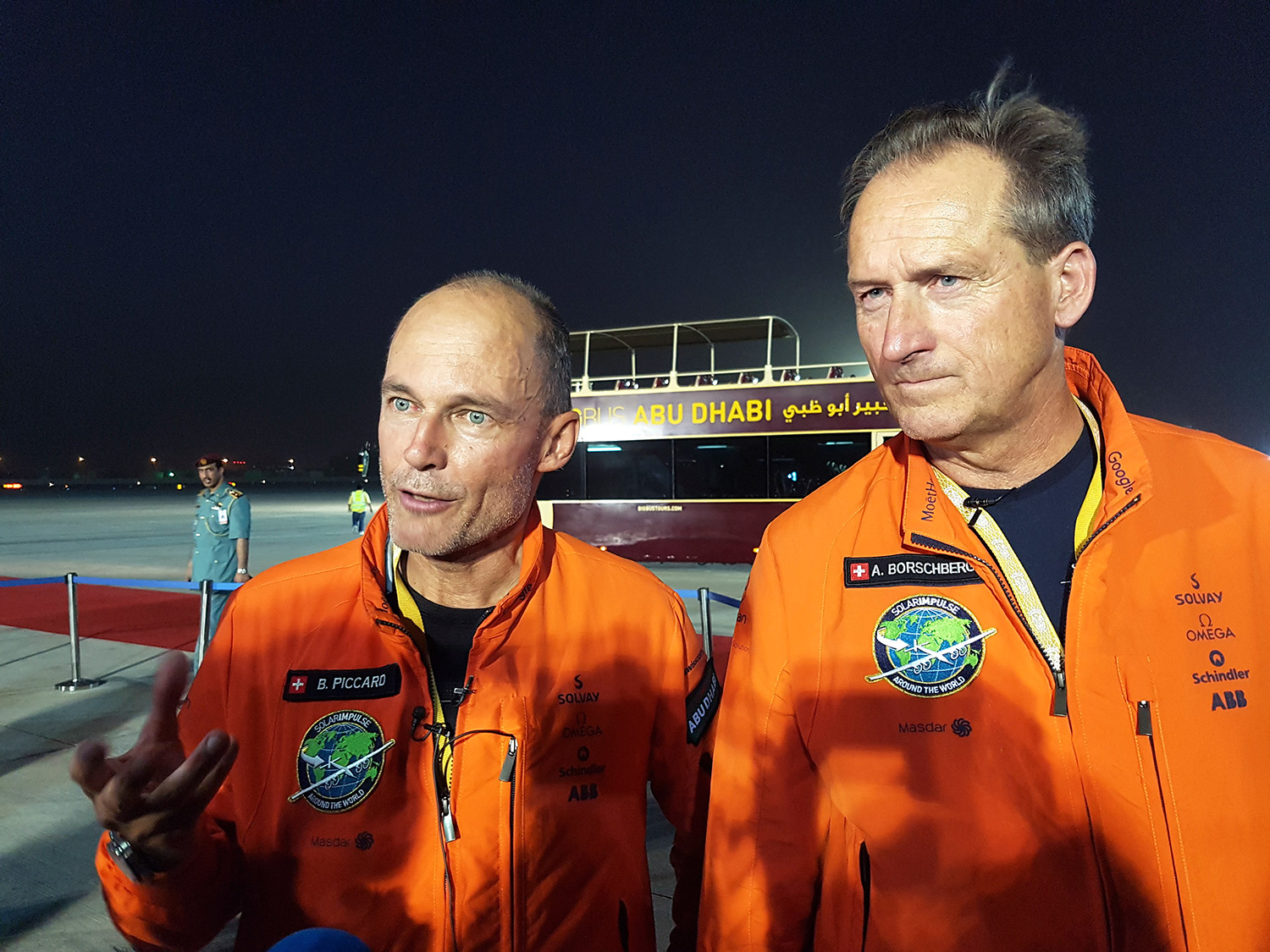 Solar Impulse 2 pilots Bertrand Piccard, left, and Andre Borschberg celebrate after their plane landed in an airport in Abu Dhabi, United Arab Emirates, early Tuesday, marking the historic end of the first attempt to fly around the world without a drop of fuel, powered solely by the sun's energy.