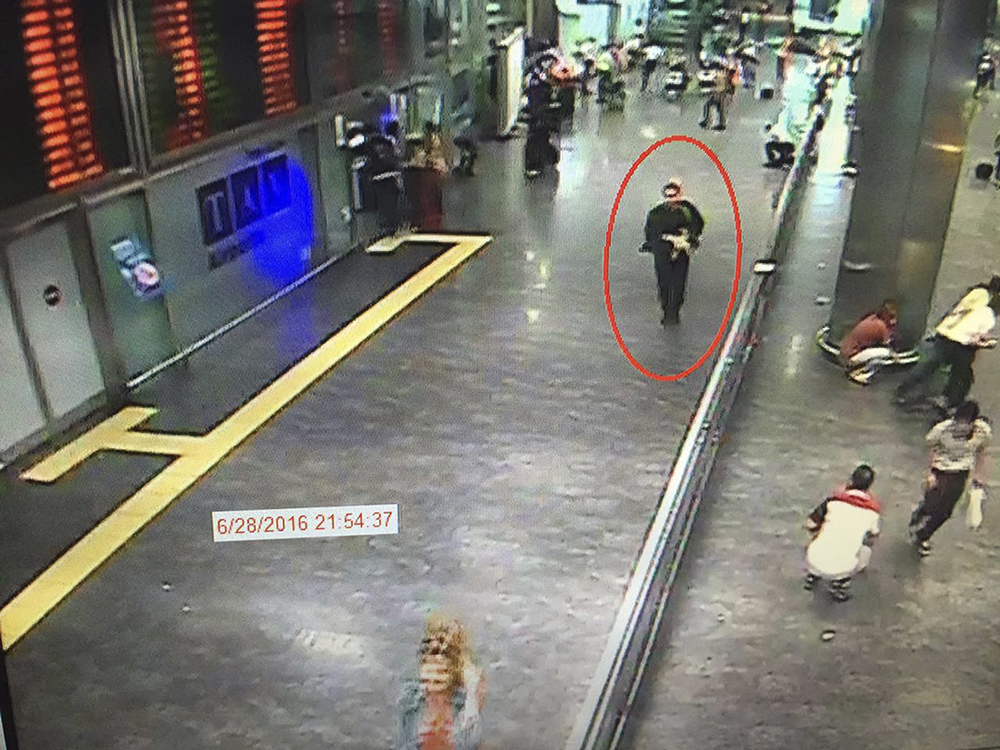 A man, circled, is believed to be among the attackers who carried out a gun-and-suicide bomb attack at Attaturk airport, killing dozens and wounding scores of others late Tuesday. Video framegrab from CCTV  made available by the Turkish Haberturk newspaper.