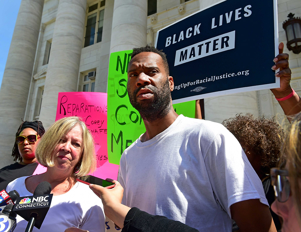 Corey Menafee, a former employee at Yale's Calhoun College who was arraigned for breaking a window depicting black slaves picking cotton, talks with the news media as he leaves New Haven Superior Court in New Haven  on  July 12, 2016. At left is his lawyer, Patricia Kane.  Peter Hvizdak / New Haven Register via AP
