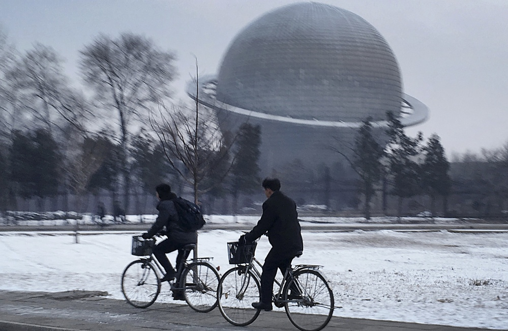 Earlier this year, North Koreans pass a planetarium in Pyongyang. The country's space officials plan to launch advanced satellites by 2020 and reach the moon in 10 years.