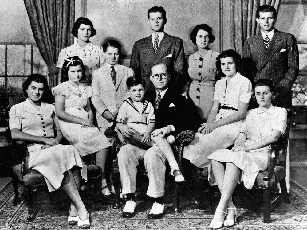 Joe and Rose Kennedy with their nine children. Bobby is wearing a light-colored suit and standing behind Ted, who is sitting on his father's lap.