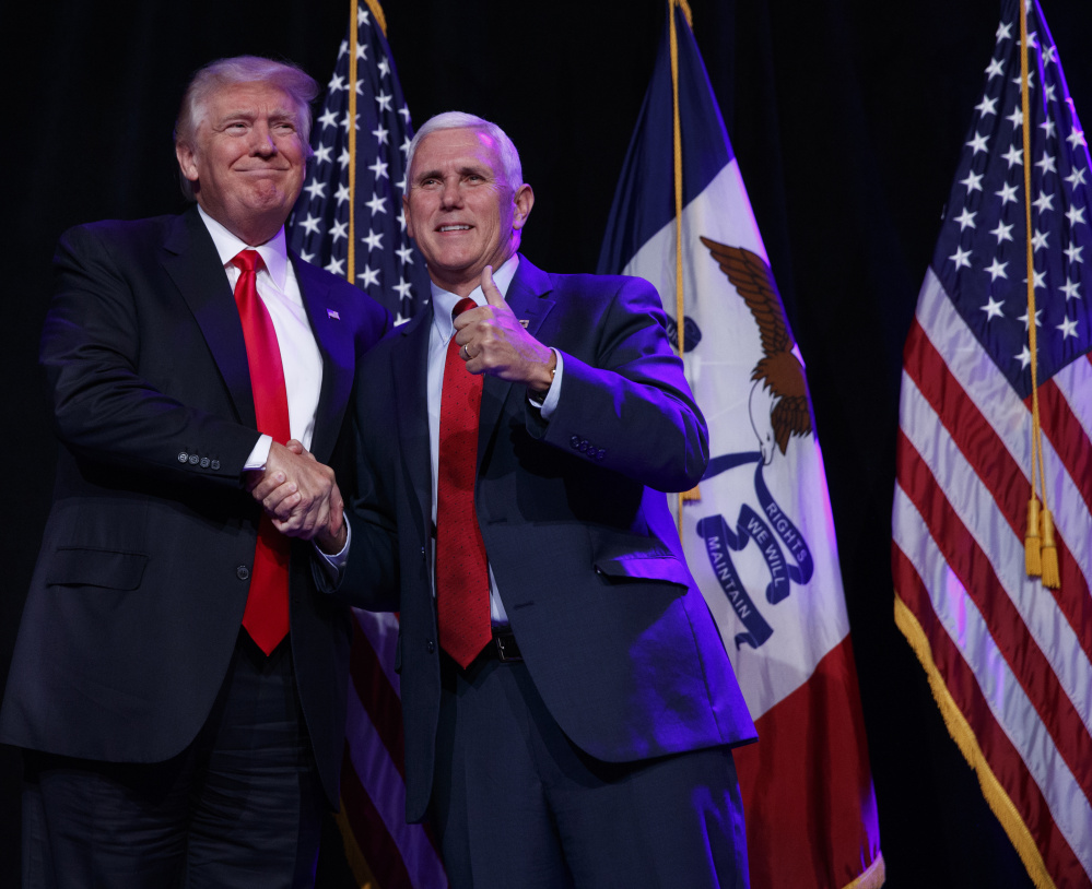 Republican presidential candidate Donald Trump shakes hands with his running mate, Indiana Gov. Mike Pence, during a campaign rally Friday in Des Moines, Iowa.