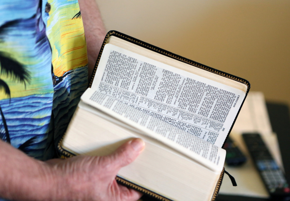 Bryon Martin flips through a Bible at his Las Vegas home, where he lives to be near the son who helped rescue him.