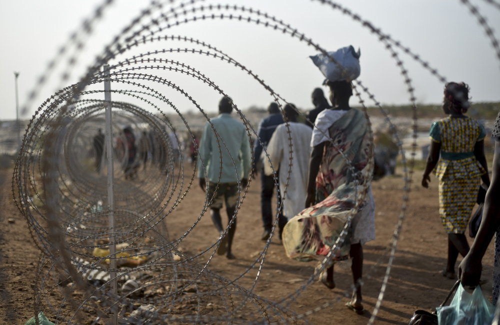 Displaced people walk next to a razor wire fence at the United Nations base in the Juba, South Sudan. The city is also a destination for girls who try to flee being sold into marriage in order to expand their family's cattle herds or to buy wives for their brothers. Associated Press/Jason Patinkin