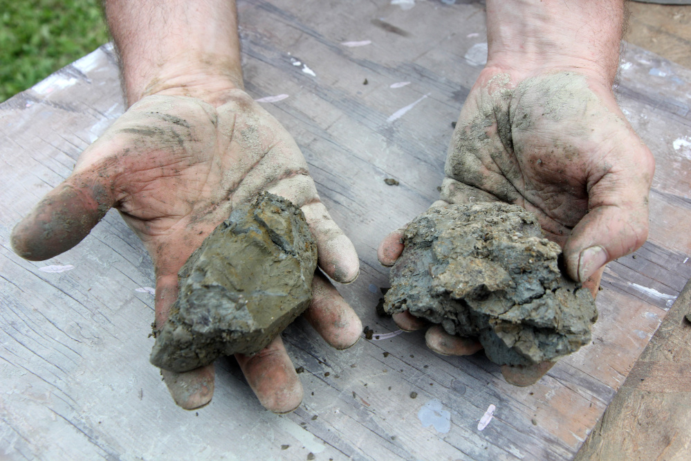 """Sam Saunders displays some """"lousy"""" clay that is mixed with sand behind Wayne Village Pottery. Saunders' family, which runs the pottery business, was hoping to dig up 40 tons of good clay on Saturday and have enough to last five to 10 years until the next dig."""