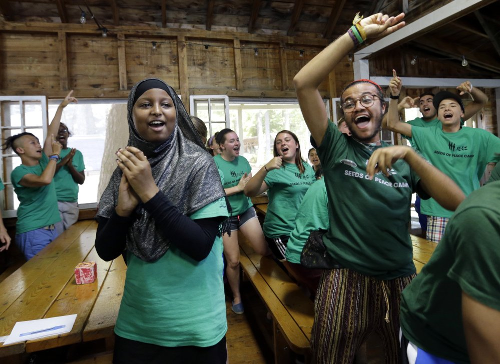 Teenagers celebrate victory in a competition at the Seeds of Peace camp in Otisfield on Friday. The lakeside camp in the woods of Maine has embarked on a pilot program this summer with teenagers from Los Angeles, Chicago and New York.