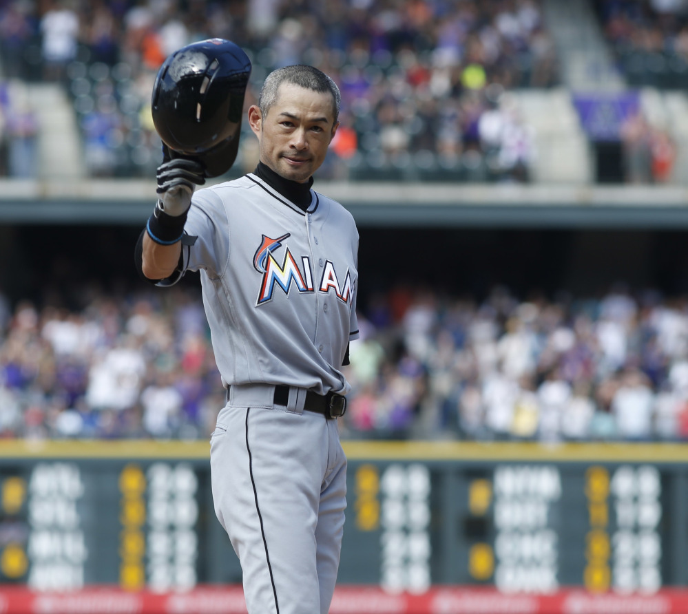 Ichiro Suzuki of the Miami Marlins tips his batting helmet to the crowd Sunday in Denver after he hit a triple for his 3,000th career hit.