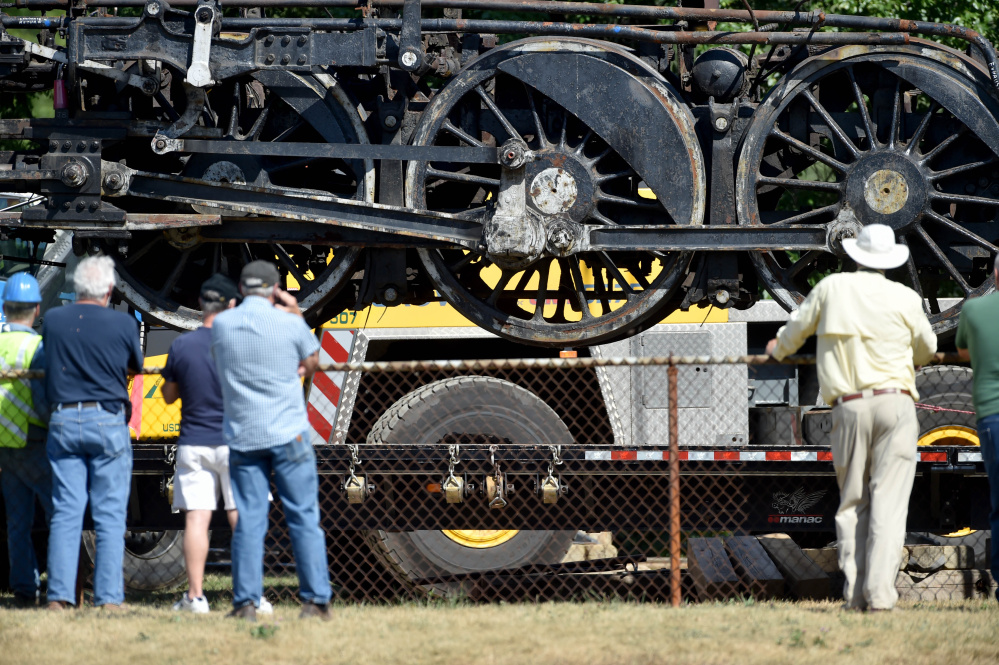 The Old 470 locomotive hangs in the air by two cranes as it is loaded onto a truck Monday to be taken to Ellsworth for a restoration project. The three-day move by the New England Steam Corporation comes after years of fundraising.