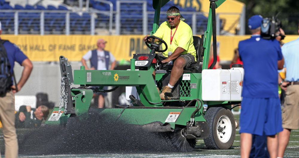 A grounds crew member tries to scrape the logo off the center of the field at Tom Benson Hall of Fame Stadium in Canton, Ohio, Sunday.