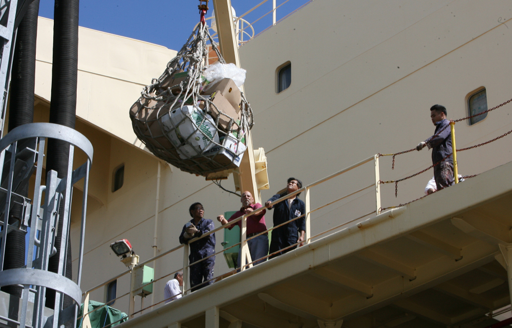 Crew members receive supplies hoisted to the Newlead Castellano on Tuesday in Savannah, Ga. The cargo vessel has been stranded near Tybee Island for nearly four months, waiting out a dispute between its Greek owner and its creditors.