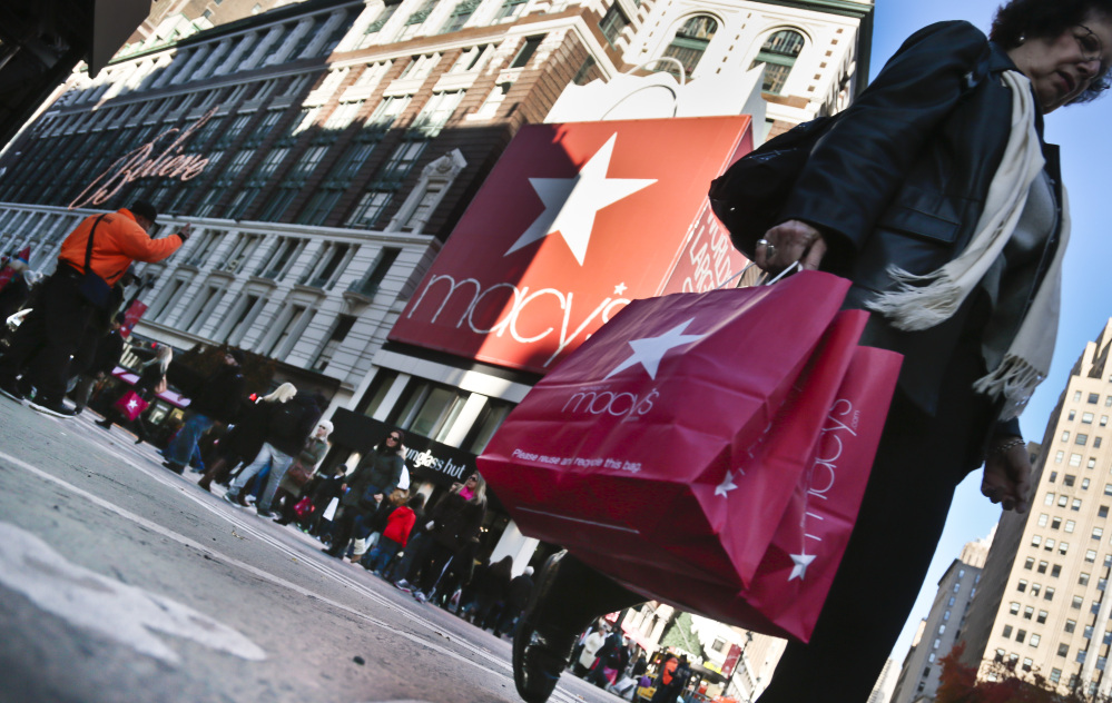 A shopper crosses an intersection with her purchases outside the Macy's store in New York City. According to its website, Macy's employs about 300 workers at its two Maine locations in South Portland and Bangor.