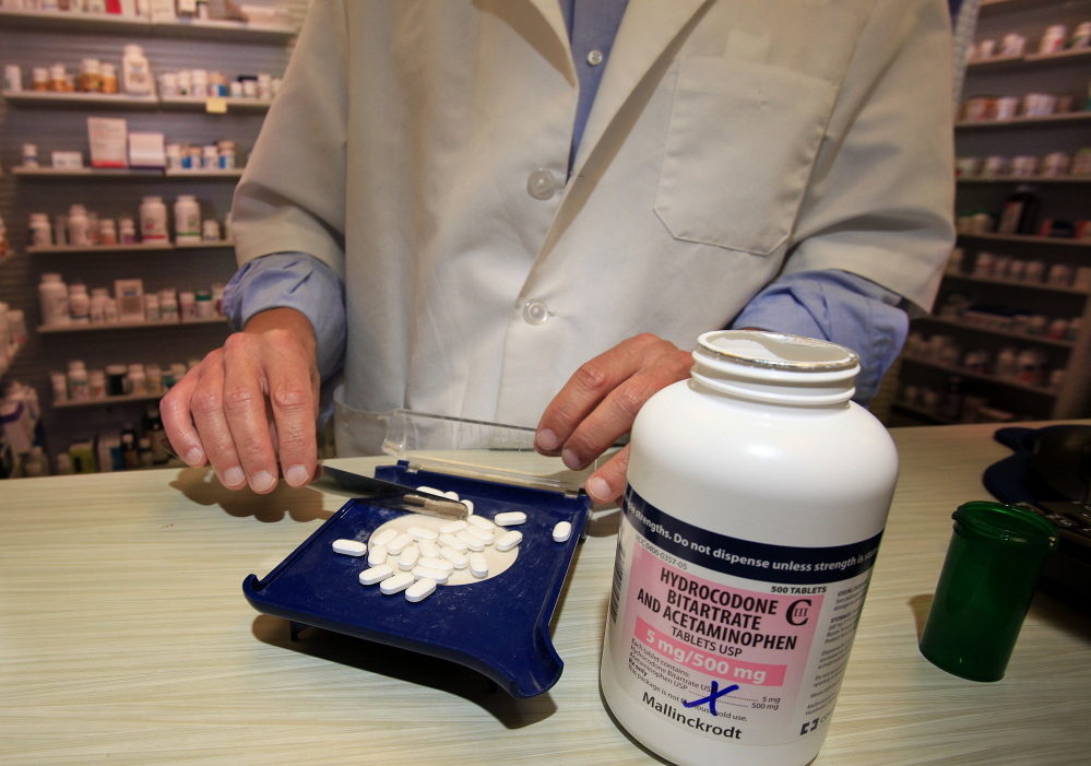 A pharmacist counts out pills of Vicodin, an opioid pain medication, in Portland. Health insurers often balk at covering the services of pain management programs that don't rely on medication.