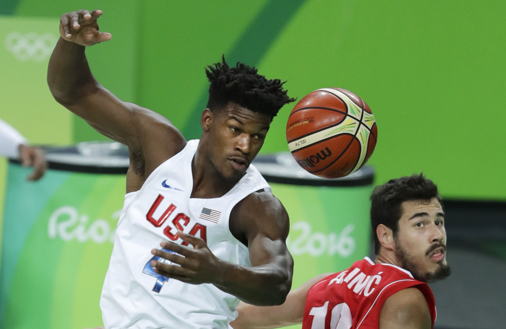 Jimmy Butler, left, of the United States fights for a rebound with Serbia's Nikola Kalinic during the Americans' 94-91 win in Olympic play at Rio de Janeiro. The U.S. has won 49 straight international tournament games.