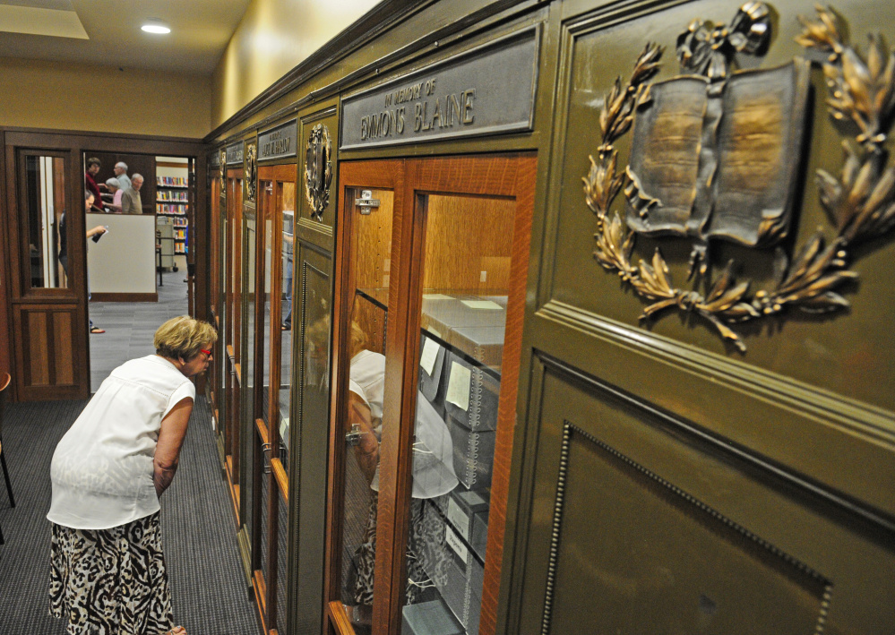 City Councilor Anna Blodgett looks at a case in a board room Saturday at Lithgow Public Library in Augusta. The metal plaques from the ends of bookcases in the 1896 section of library are displayed in the small first-floor meeting room.