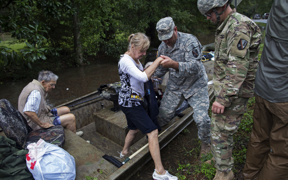 Members of the Louisiana Army National Guard rescue people from rising floodwater Sunday near Walker, La., after heavy rains inundated the region. With several rivers still rising, there is danger of more flooding.