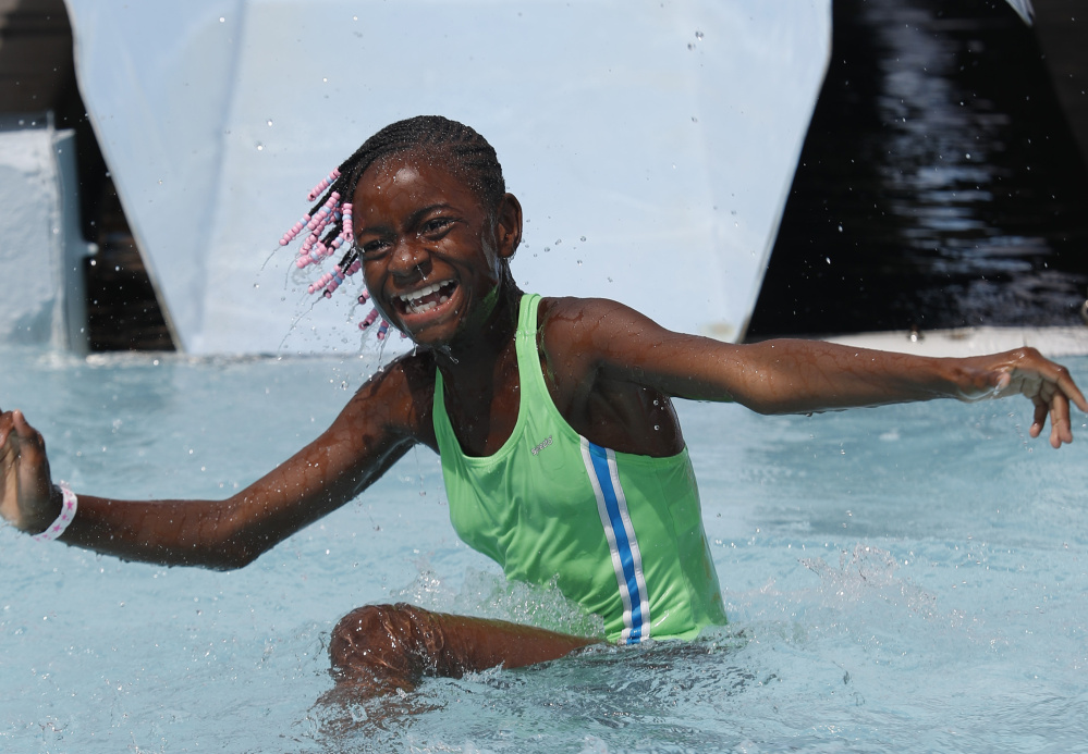 Malaysia White, 11, a Fresh Air Fund child from New York City, smiles after reaching the bottom of a water slide Sunday.