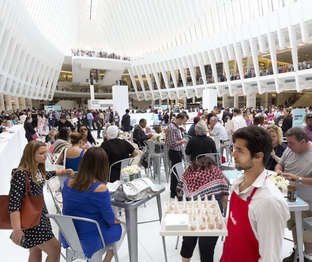 A waiter carries a tray in the World Trade Center Transportation Hub on Tuesday in New York as the new – and reinvented – mall there opens. A wide variety shops and restaurants serve the needs of a much larger and more diverse clientele.