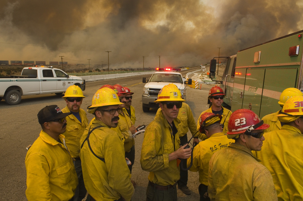 A U.S. Forest Service crew looks for routes to aid in battling a wildfire near Highway 138 and Interstate 15 in California.