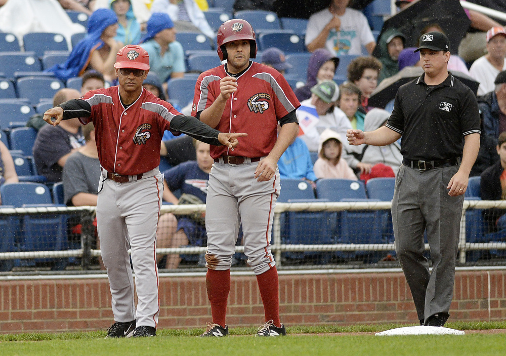Altoona manager Joey Cora, left, gives instructions from the third base box during  Tuesday's game. On third base is Altoona's Christopher Diaz.
