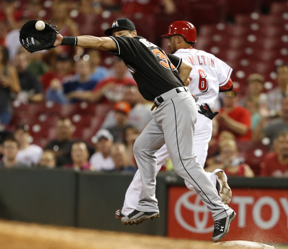 Cincinnati's Billy Hamilton beats the throw to Marlins first baseman Derek Dietrich for a single, setting up the Reds' seventh-inning rally in a 3-2 win.