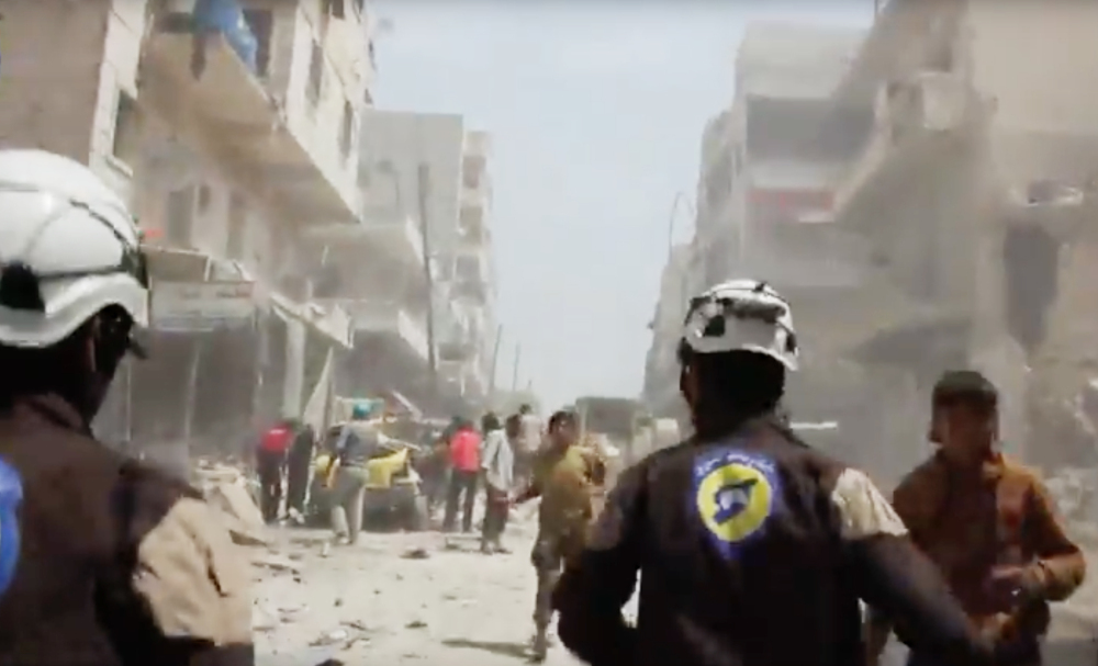 Civil defense workers , also known as the White Helmets, run to help the injured after airstrikes and shelling in Aleppo, Syria, in April.