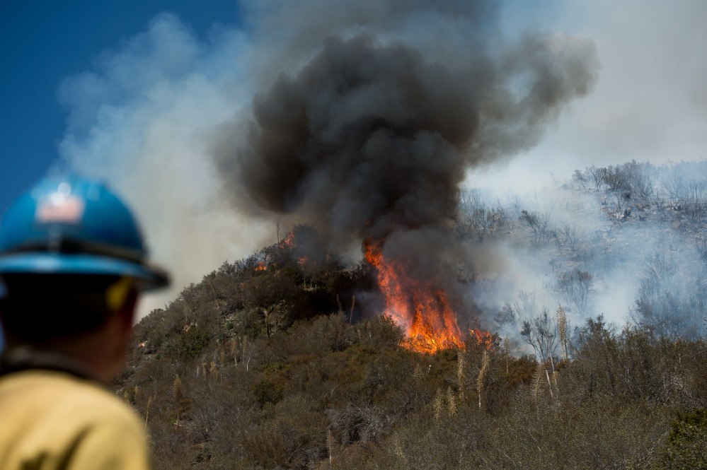 Firefighter Tyler Jaquess of the Del Rosa Hot Shots monitors the Blue Cut fire as it burns near Wrightwood, Calif. The blaze destroyed at least 96 homes and 213 outbuildings.