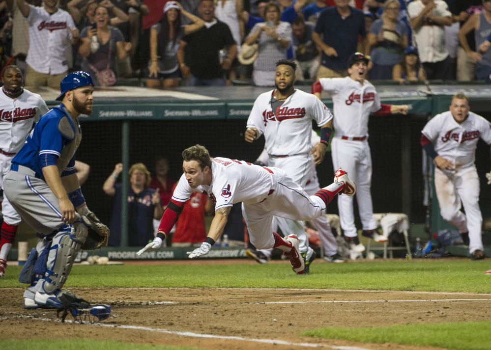 Tyler Naquin, slides into home plate for an inside-the-park home run as Blue Jays' catcher Russell Martin waits for the throw Friday in Cleveland. Naquin's homer gave the Indians a 3-2 win.