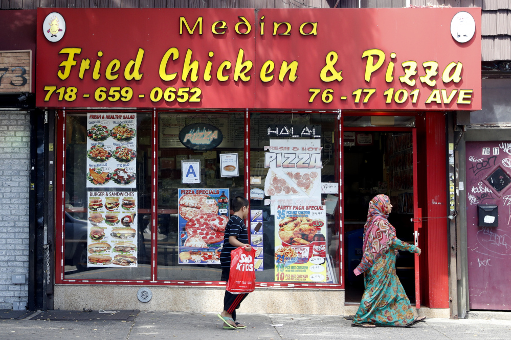 A Muslim mother and son walk past a Halal restaurant in the Ozone Park section of Queens, N.Y.